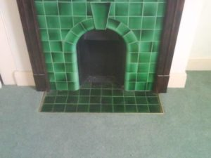 A traditional carpet laid in a traditional room with a lovely tiled fireplace.